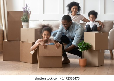 Overjoyed african family enjoy relocation day at new modern house, father push daughter sitting inside of carton box having fun riding in cozy living room, loan mortgage, housing improvement concept