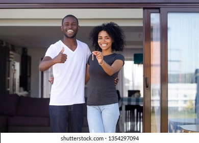 Overjoyed african married couple standing on summer terrace porch near new modern house. Happy wife hold keys embracing beloved husband showing thumbs up sign. Property ownership, loan tenancy concept