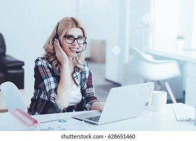 Overjoyed beautiful female support operator sitting in the office
