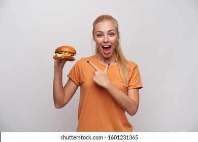 Overjoyed beautiful young blonde female with ponytail hairstyle looking at camera with wide eyes and mouth opened and showing on tasty hamburger in her hand, isolated over white background