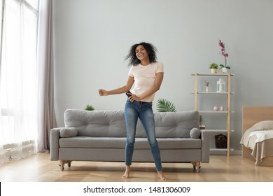 Overjoyed black biracial millennial girl dancing alone moving to rhythm in living room, happy african American young woman have fun enjoying listening to music, entertain on weekend at home - Shutterstock ID 1481306009