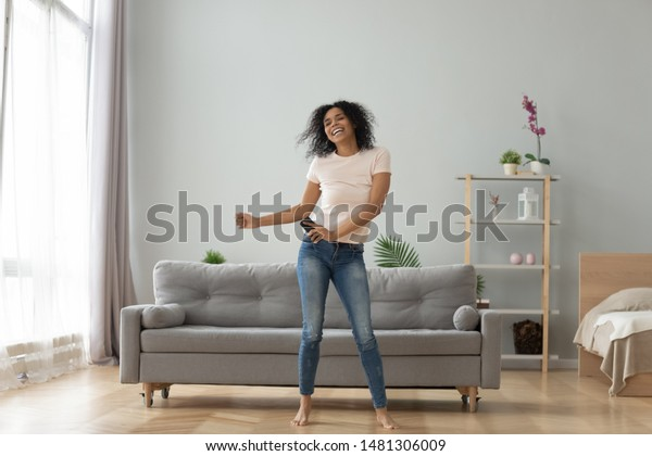 Overjoyed black biracial millennial girl dancing alone moving to rhythm in living room, happy african American young woman have fun enjoying listening to music, entertain on weekend at home