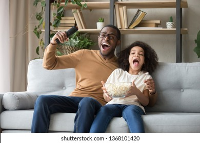 Overjoyed black family sitting on sofa watch football sport tv game feels happy excited celebrating cheering soccer victory last minute goal dad kid eating popcorn enjoy time at home together concept