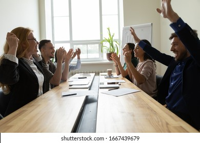 Overjoyed businesspeople sit at desk in office celebrate shared business company victory, happy diverse colleagues or employees raise hand motivated for good result, engaged in teambuilding activity