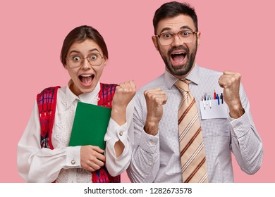 Overjoyed clumsy woman and man nerds clench fists, celebrate finishing preparing for seminar, wear spectacles, elegant old clothes, carry textbook, express good emotions, stand over pink background