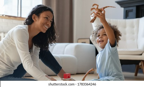 Overjoyed cute little biracial boy baby child play rubber dinosaur with happy loving young mom, smiling african American mother and small ethnic son kid engaged in funny fame with toys at home