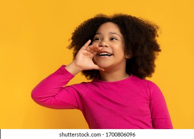 Overjoyed cute little black child holding hand near mouth, making announcement, screaming aside at copy space on yellow background