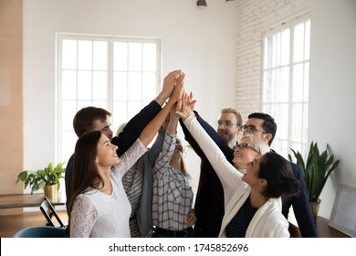 Overjoyed different ages mixed race teammates raising joined hands, giving high five to each other, celebrating company business success achievement, involved in team building activity in office.