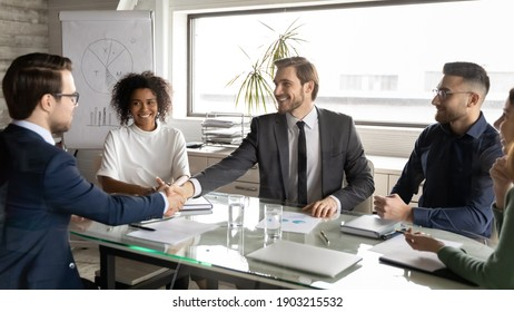Overjoyed diverse business people greeting new member at meeting in boardroom, handshake, smiling executive team leader shaking businessman hand, business partners making deal, great agreement