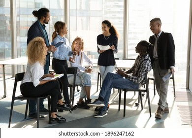 Overjoyed diverse multiethnic employees talk speak at team meeting in modern office. Smiling multiracial colleagues have fun brainstorming discussing business project in group briefing together.