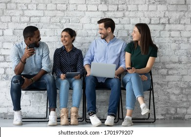 Overjoyed diverse young people sit in queue on chairs have fun waiting for office interview, happy multiracial candidates use electronic devices preparing for recruitment talk, employment concept