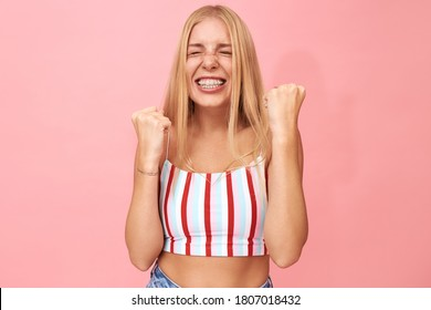 Overjoyed ecstatic girl with long straight hair clenching fists and screaming Yes, being excited because being accepted to top university. Life goals, success, achievement and victory concept