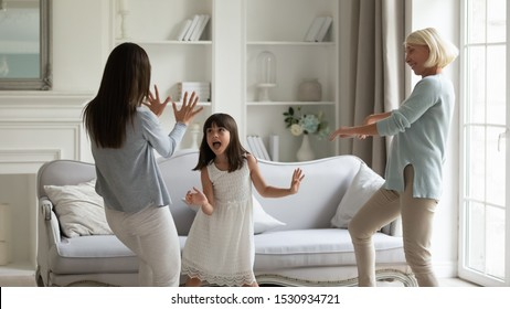 Overjoyed energetic little preschool girl having fun with young mother and funny middle aged granny in living room. Happy 3 generations family dancing to favorite music, spending active time together.