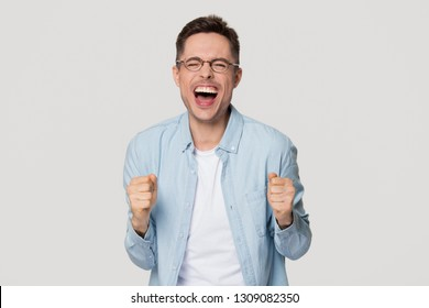 Overjoyed excited funny young man nerd screaming with joy celebrating win isolated on white grey studio background, happy lucky guy winner in glasses motivated by success victory goal achievement