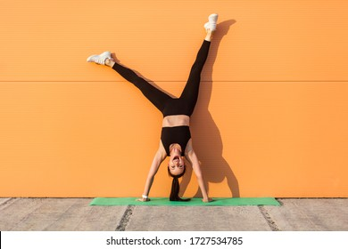 Overjoyed excited girl with perfect athletic body in tight sportswear doing yoga handstand pose against wall and laughing, shouting from happiness. Gymnastics for body balance outdoor workouts