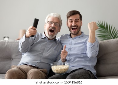 Overjoyed excited two generations men family old senior father and young adult grown son hold snack remote control watching tv sport game match scream support celebrate team victory at home on sofa