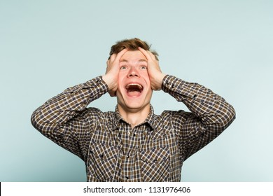 overjoyed extremely happy and excited man clutching his head. portrait of a young guy on light background. emotion facial expression. feelings and people reaction.