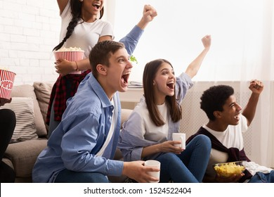 Overjoyed football fans watching match on tv and celebrating victory at home eating chips and popcorn
