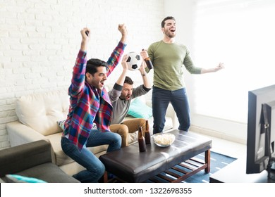 Overjoyed friends celebrating victory of favorite soccer team in living room