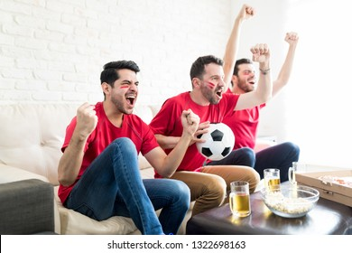 Overjoyed friends with soccer ball showing their uncontrollable joy at home