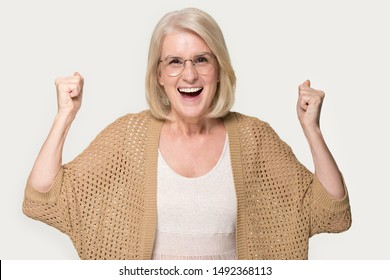 Overjoyed funny mature lady isolated on grey studio background feel euphoric win online lottery, excited senior woman wear glasses and cardigan look at camera triumph gain victory, hear good news
