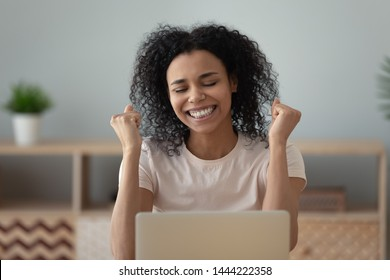 Overjoyed happy african black girl student winner read good internet news celebrate success victory excited by online bid win get great exam results scholarship sit at home office desk with laptop