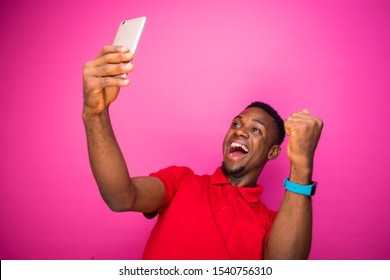 overjoyed happy african male  holds modern mobile phone excited to receive text message informing about salary standing indoor on a pink wall. reaction concept