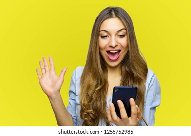 Overjoyed happy excited female glad to recieve text message informing about salary, rejoices good news, stares at mobile phone, gestures actively from happiness, stands indoor alone. Reaction concept.