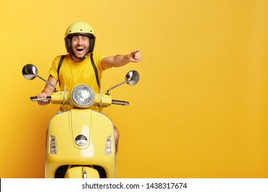 Overjoyed happy male drives motocycle, dressed in casual yellow t shirt and headgear, points happily into distance, notices something awesome, reaches destination on fast transport, enjoys speed