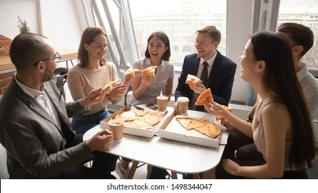 Overjoyed happy mixed race company employees gathered at office table, celebrating special occasion, eating delivery Italian fast food, talking, storytelling, joking, bursting in laugh, having fun.