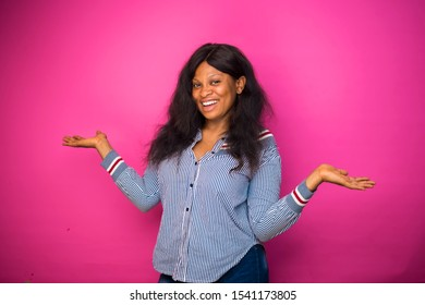 overjoyed Happy plus-size lady excited wearing oversized T-shirt and blue jeans on a pink wall leaving space for advertisement. reaction concept