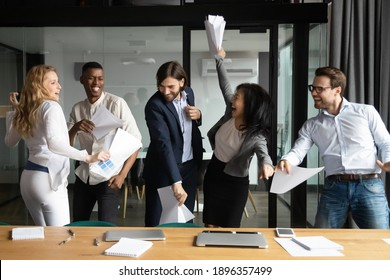 Overjoyed happy young and senior multiracial diverse business people colleagues celebrating corporate success, workday finish or closing profitable deal, dancing and having fun together in office.