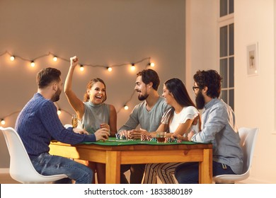 Overjoyed, happy young woman laughing and raising arm, celebrating her victory in game of poker, sitting at table with friends at casino themed party at home or club