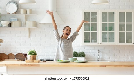Overjoyed happy young woman raise hands feel excited cooking alone in modern kitchen interior, funny independent girl dancing prepare dinner at home having fun enjoy freedom healthy lifestyle concept