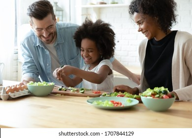 Overjoyed international young family with little daughter have fun preparing healthy food salad at home together, happy multiracial parents teach small girl child cooking in kitchen on weekend