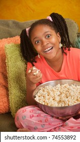 Overjoyed little African American girl with a bowl of popcorn