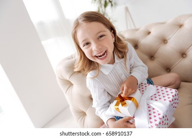 Overjoyed little girl holding a pile of presents
