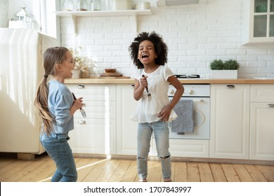 Overjoyed little multiracial sisters have fun play singing in kitchen appliances together, happy small multiethnic girls siblings engaged in funny activity at home enjoy leisure weekend or quarantine