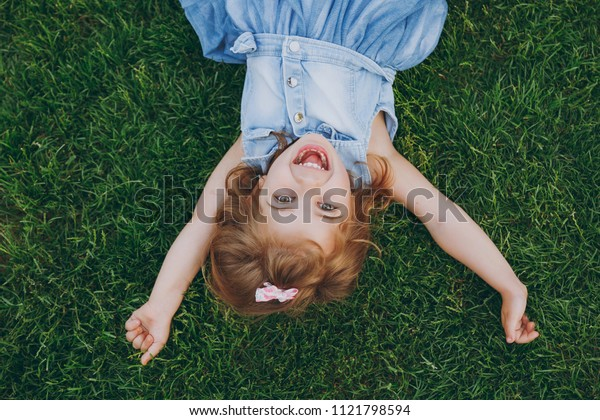 Overjoyed little pretty child baby girl in light dress lie on green grass lawn, spreading hands in park. Mother, little kid daughter. Mother's Day, love family, parenthood, childhood concept