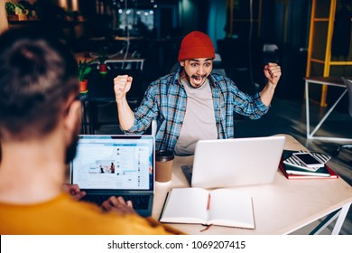 Overjoyed male football fan amazed with victory of team watching match screaming and cheer up during working process, emotional hipster guy raising hands  celebrating great news of winning in contest
