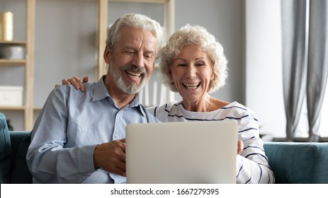 Overjoyed mature 60s husband and wife sit relax on sofa in living room have fun watch funny video on laptop, smiling elderly couple rest on couch browse internet use modern computer at home together