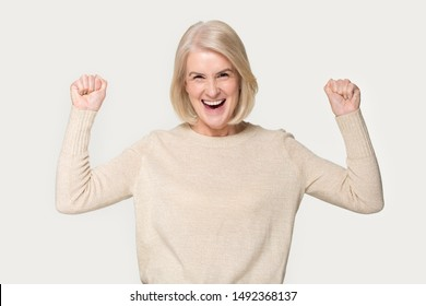 Overjoyed mature old woman isolated on grey studio background raise hands triumph with online lottery win, excited aged senior female look at camera scream yes feel euphoric with victory or reward