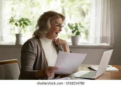Overjoyed mature woman wearing glasses reading good news in message, looking at laptop screen, amazed elderly female received great sale offer, money refund, holding document, checking loan agreement