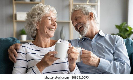 Overjoyed middle aged retired married couple relaxing on comfortable sofa, enjoying communicating while drinking hot morning coffee together at home, laughing at funny joke, family relations concept.