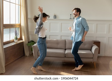 Overjoyed millennial Caucasian couple renters or buyers have fun celebrate relocation to new home together. Happy young man and woman tenants dance in living room, enjoy weekend in own house.