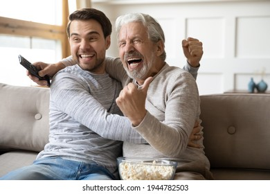 Overjoyed millennial Caucasian man and mature father relax at home watch football match online celebrate goal win. Happy older dad and adult grownup son enjoy team victory enjoying game on TV.