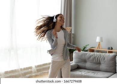 Overjoyed millennial girl wearing headphones have fun moving listening to music relax in living room, happy young woman in earphones dance enjoy leisure weekend at home, stress free concept - Shutterstock ID 1667279608
