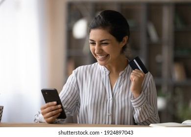 Overjoyed millennial Indian woman use smartphone shopping online with credit card. Excited young mixed race female buyer get good sale deal or promotion offer buy on internet on cellphone gadget.