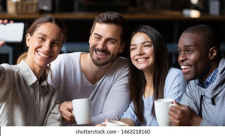 Overjoyed millennial multiracial friends gather in coffeeshop smiling for self-portrait picture on cellphone together, happy diverse young people have fun meeting in cafe making selfie on smartphone