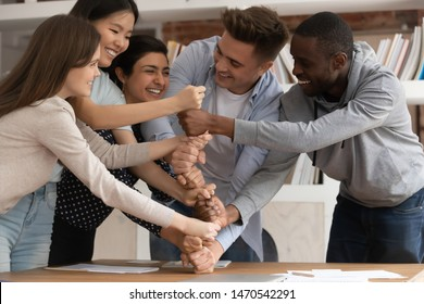 Overjoyed mixed race young students involved in funny game or teambuilding activity, making fists pyramid. Happy smiling diverse young people demonstrating multiracial unity, support and cooperation.